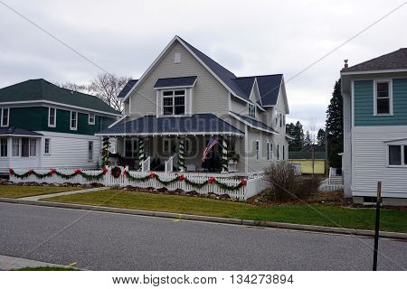 HARBOR SPRINGS, MICHIGAN / UNITED STATES - DECEMBER 24, 2015: A home on Fourth Street is decorated with garlands and ribbons for Christmas in Harbor Springs.