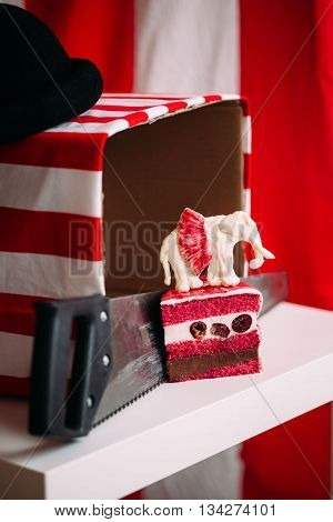 red velvet cake, cut, on a red-and-white background, in the style of a circus, is on the saw