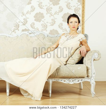 Stylish woman in a evening gown in a luxurious interior