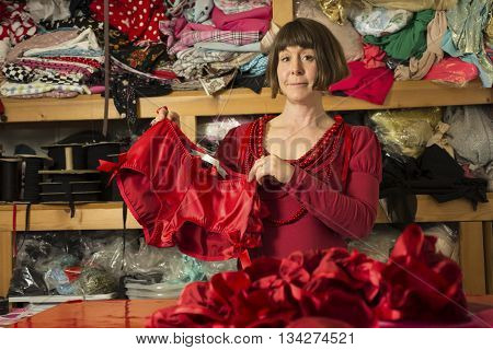 A woman tailor in red dress displaying newly sewn red knickers