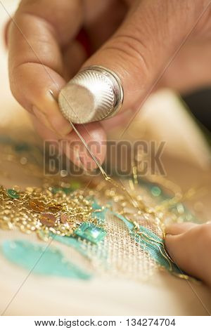 Close up shot of a ladies hands wearing a thimble and doing delicate embroidery with gold thread and sequins
