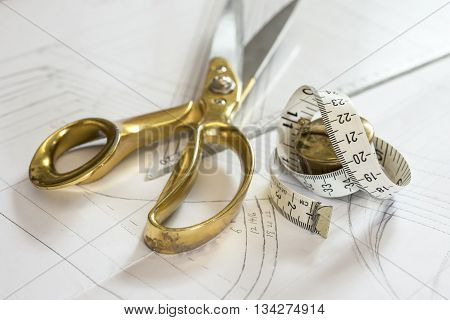 A tape measure beside a pair of brass-handled scissors on a plastic triangle rule