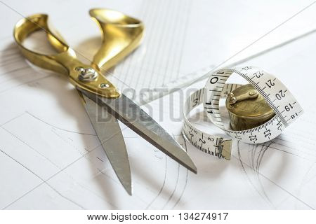 A pair of brass-handled tailor shears plastic triangle rule and a roll of tape measure.