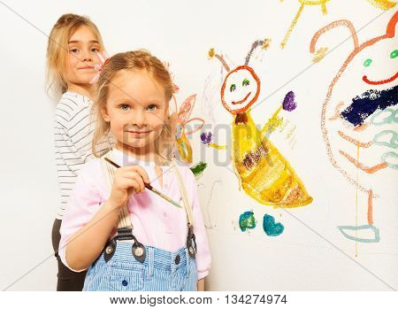 Two little girls with brushes drawing funny bugs, isolated on white