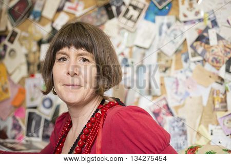 A lady in red blouse and necklaces smiling and staring straight at the camera with wall of photos and cards in the background.