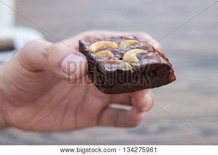 A piece of homemade chocolate brownie with cashew nut in left hand.