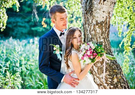 Young wedding couple near birch tree outdoor