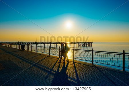 People walking on the embankment at Baltic Sea coast at sunset