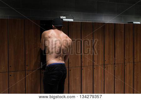 Adult Man In Locker Room Opening Locker Door