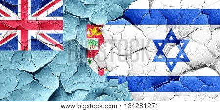 Fiji flag with Israel flag on a grunge cracked wall