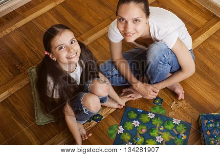 daughter and mother sitting on the floor with a board game