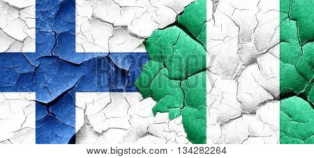 finland flag with Nigeria flag on a grunge cracked wall
