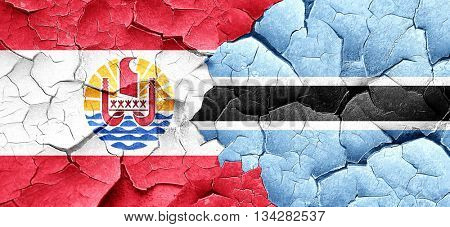 french polynesia flag with Botswana flag on a grunge cracked wal