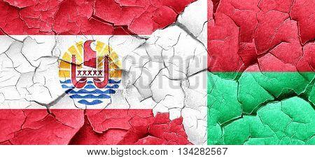 french polynesia flag with Madagascar flag on a grunge cracked w