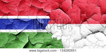 Gambia flag with Indonesia flag on a grunge cracked wall