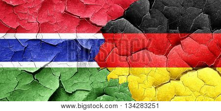 Gambia flag with Germany flag on a grunge cracked wall