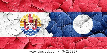 french polynesia flag with Laos flag on a grunge cracked wall