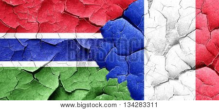 Gambia flag with France flag on a grunge cracked wall