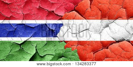 Gambia flag with Austria flag on a grunge cracked wall