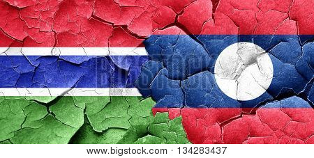 Gambia flag with Laos flag on a grunge cracked wall