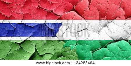 Gambia flag with Hungary flag on a grunge cracked wall