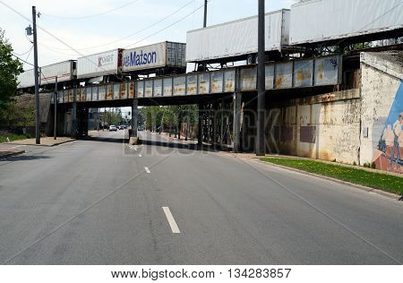 JOLIET, ILLINOIS / UNITED STATES - MAY 3, 2015: A freight train crosses a bridge over Scott Street near downtown Joliet, Illinois.