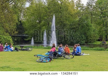 AMSTERDAM, NETHERLANDS - MAY 9, 2013: Group unknown young people are resting on the shore of the pond in Vondelpark.