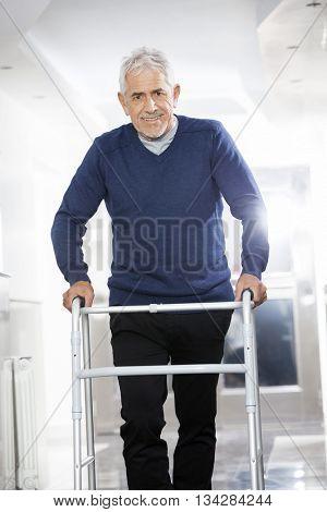 Senior Male Patient Using Walker At Rehab Center