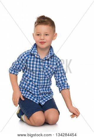 Elegant little boy in a plaid shirt kneeling on the floor- Isolated on white background