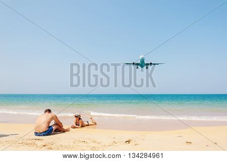 Phuket Thailand - March 10 2016: Beach near the airport Plane come in the land with some people and blue sea and white sand beach