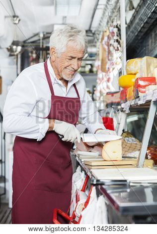Happy Salesman Slicing Cheese In Shop
