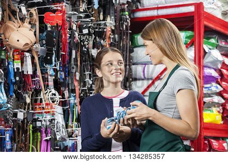 Smiling Girl Buying Toy From Saleswoman In Pet Store