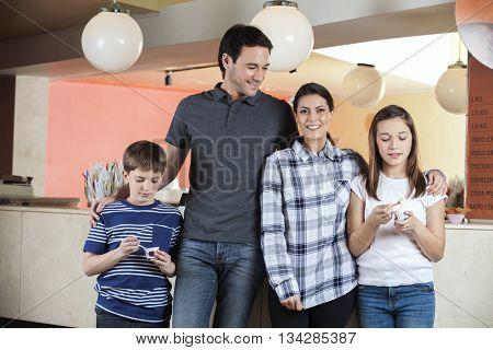 Couple Standing With Children Having Ice Cream