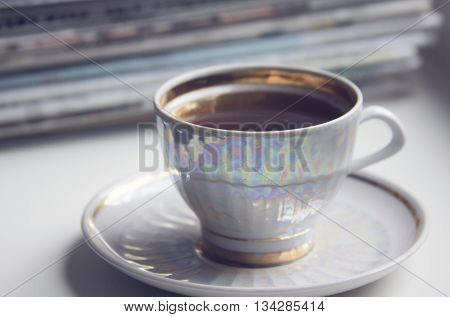 Cup of coffe (espresso) on the saucer in front of newspapers in the morning before business