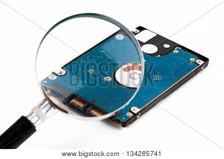 Magnifying Glass Over A Computer Harddrive. Hard Disk Of A Laptop.