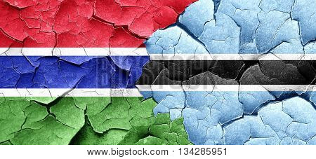 Gambia flag with Botswana flag on a grunge cracked wall