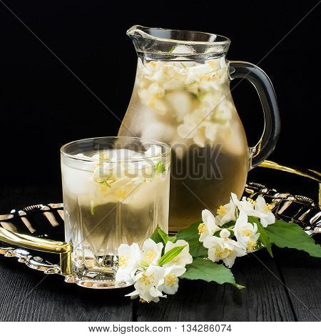 Refreshing cold green tea with jasmine and ice in a jug and a glass. Square image