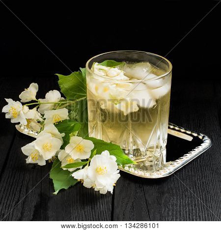 Refreshing cold green tea with jasmine and ice in a glass. Square image