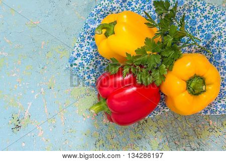 Fresh organic red and yellow bell peppers and parsley on old blue table
