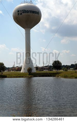 SHOREWOOD, ILLINOIS / UNITED STATES - AUGUST 16, 2015: The Shorewood Water Tower towers over a retention pond in Shorewood.
