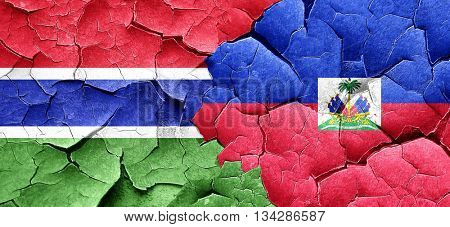 Gambia flag with Haiti flag on a grunge cracked wall