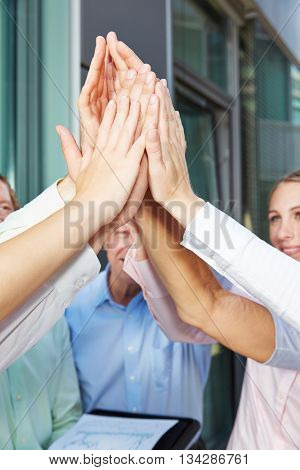 Many hands clapping high five in a business people team