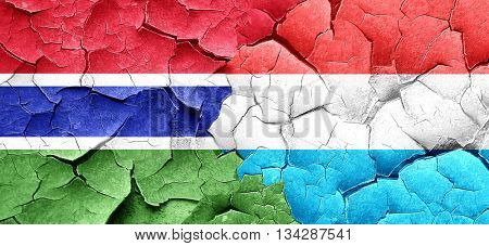 Gambia flag with Luxembourg flag on a grunge cracked wall