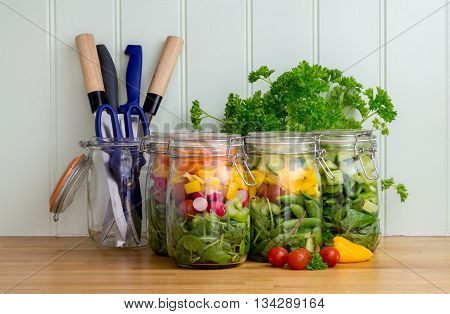 Prepared salad in glass storage jars with knives and scissors on a kitchen worktop.
