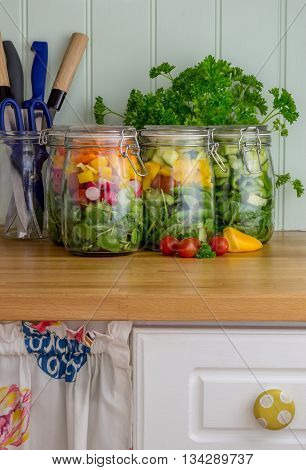 Prepared salad in glass storage jars with knives and scissors. In kitchen.