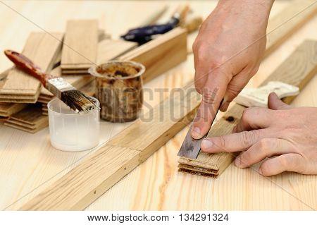 Carpenter hands at work with chisel closeup