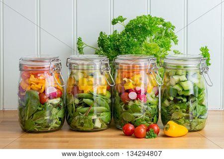 Four prepared salads in glass storage jars in a neat row.