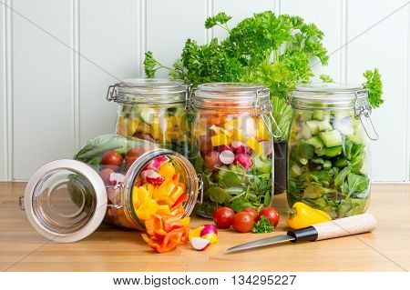 Prepared salad in glass storage jars.One jar tipped on side spilling contents.