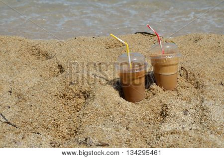Cold coffee frappes set on beach with sea in background