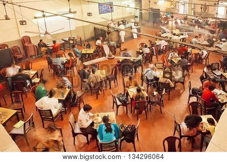 KOLKATA, INDIA - JAN 15, 2016: People having breakfast inside traditional Indian Coffee House on January 15, 2016. The India Coffee House chain was started by the Coffee Cess Committee in 1936 in Mumbai